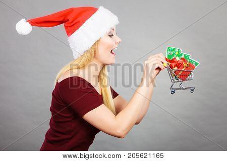 Xmas seasonal shopping winter celebration concept. Happy woman wearing Santa Claus helper costume holding trolley cart with little christmas tree inside.