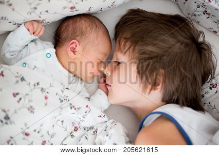 Bbeautiful Boy, Hugging With Tenderness And Care His Newborn Baby Brother At Home
