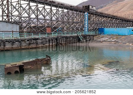 Pyramiden Norway - August 2017: Abandoned Soviet/ Russian settlement Pyramiden in Svalbard archipelago. Monument with settlement's name in the harbour sunken ship in the sea and pier.