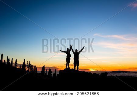 Teamwork couple climbing and reaching mountain peak. Silhouette of climbers team over mountains sunset. Man and woman hikers looking at inspirational landscape on Tenerife Canary Islands Spain.