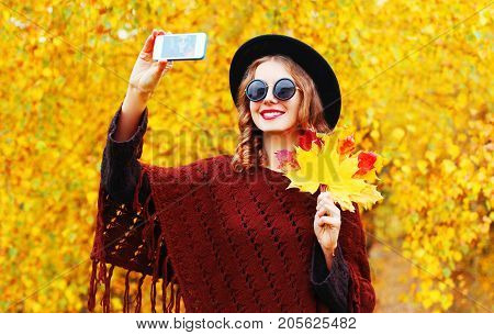 Autumn Fashion Smiling Young Woman Taking A Picture Self Portrait On The Smartphone In Knitted Ponch