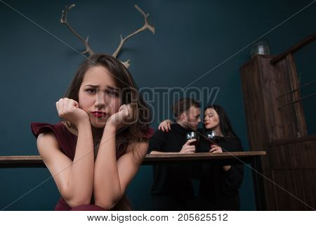 Cheating relationships. Unhappy betrayed girl. Love affair behind back, male cheater with friend. Unfaithful partner, pretty female with horns on blue background in focus on foreground