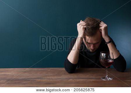 Despondent drunk young man in bar. Sad thoughtful male on blue background with free space, troubles in life with red wine. Unlucky date, bad habits, breakup