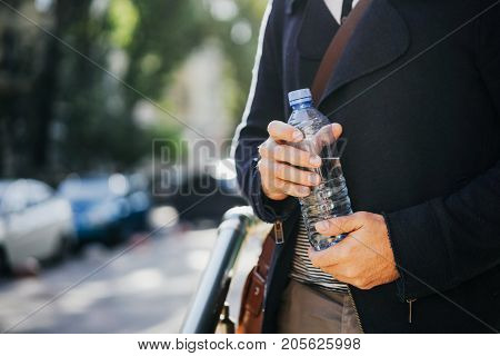 bottle of fresh drinking water in the hands of men on the street. To quench your thirst.