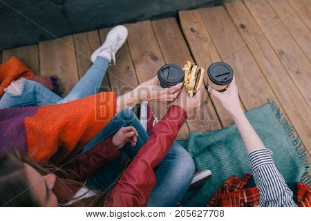 Meeting old friends on roof, top view. Takeaway junk food as celebration meals, friendship, rest and communication, sharing time together, cheerful and joyful atmosphere
