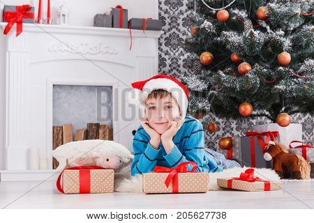 Cute dreamy boy in santa hat unwrap christmas present box on holiday morning in beautiful room interior. Male child open Xmas gifts near big decorated fir tree and fireplace. Winter holidays concept
