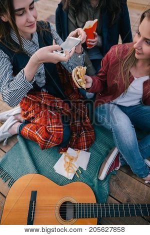 Girls making photo of fast food by smartphone. Close up of friends meeting, outdoor rest and communication, sharing time together, cheerful atmosphere with music