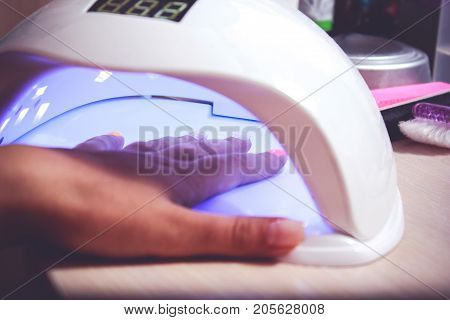 Closeup of the hand of a woman inside a UV or LED lamp curing her recently applied gel nail polish at a salon