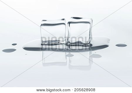 Melting ice cubes with reflection on white background. Closeup of cold crystal blocks group cutout