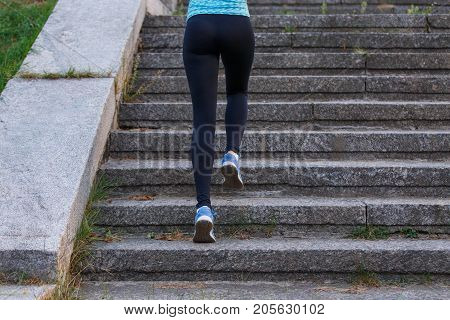 Young sporty woman ascending on stairs training in the morning. Fitness girl going up stairs jogging in park
