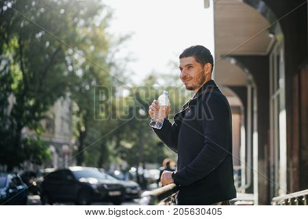 portrait of a young man with a bottle of drinking mineral water on the background of the city and the streets at noon.