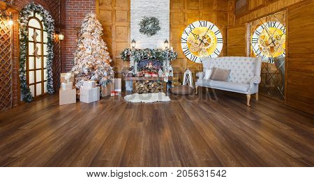 Beautiful christmas interior. Warm room with fireplace, decorated christmas tree, lots of presents and huge clock on wooden wall. Cozy home for winter holidays, copy space