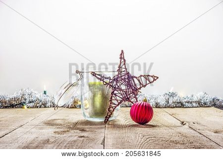Handmade Wooden Star, Red Ornament And Green Candle In Jar On Rustic Wooden Surface With Tinsel And