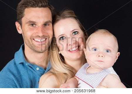 Close-up Of Happy Parents Holding Their Newborn Baby