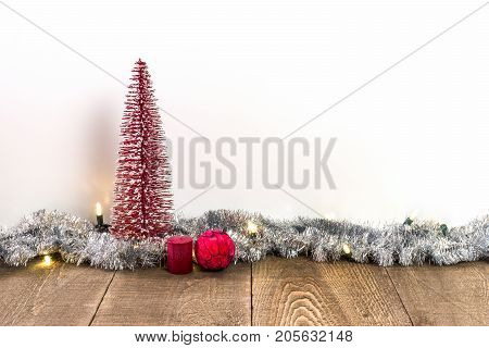 Red Decorative Christmas Tree With Candle And Ornament On Rustic Wooden Table, Tinsel And Lights