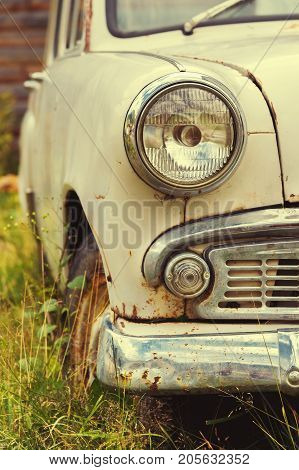 The old rusted machine. Front view where there is a headlight with a grille and a bumper. Vintage concept