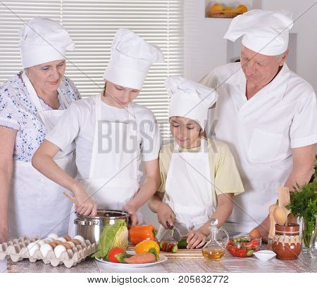 grandparents with grandsons cooking together at kitchen