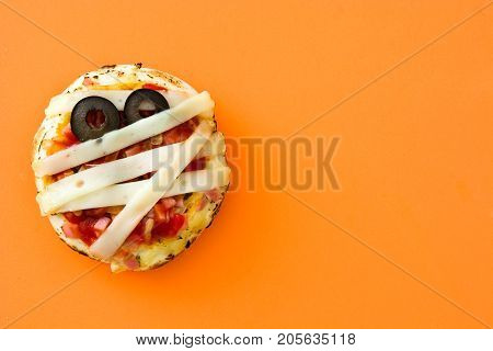 Halloween mummies mini pizzas on orange background