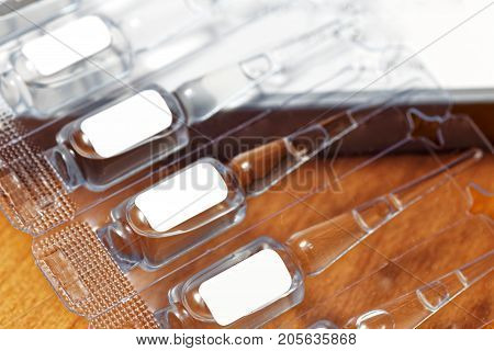 Pack of plastic ampoules with medicines or cosmetics facial skin care product. Blank white labels with copyspace. Shallow focus.