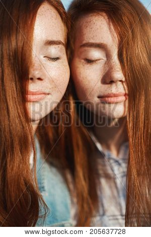 Portrait of ginger twin sisters with eyes closed. Enjoying their sisterhood and friendship. Older and younger sister living happily.
