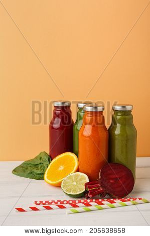 Healthy food. Assortment of fruit and vegetables detox smoothies with ingredients in glass bottles on pastel orange wall background, copy space.