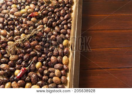 Baking, roasting raw, fresh, colorful, organic olives, with rosemary, red hot peppers and mediterranean herbs, close-up, selective focus, space for text