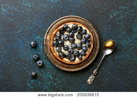 Blueberry tart, pie, tartlet with custard on blue stone background with copy space.
