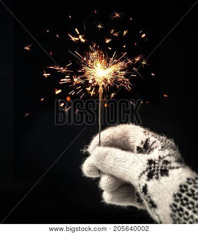 Festive Merry Christmas sparklers. Golden Magic lights for holiday poster birthday or party concept. Hand holding Sparkling beautiful sparkles or bengal lights