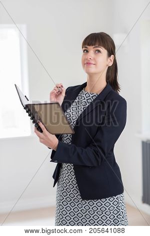 Female Estate Agent Looking Around Vacant Property For Valuation