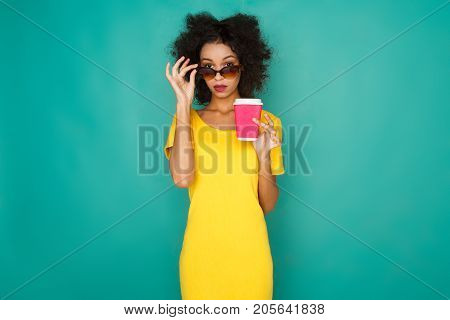 Curly concerned mulatto girl in bright yellow dress and sunglasses with take away coffee cup. Young woman at azur studio background looking questioningly from under her dark glasses, copy space poster