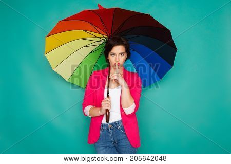 Stylish girl in bright casual clothes under rainbow colored umbrella showing hush, be quiet at azur studio background, copy space