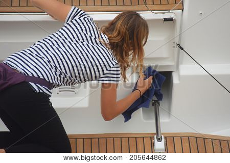 A girl, keeps the yacht clean  that is anchored at the dock