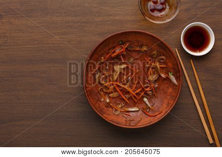 Empty plate after dinner, leaving only the crumbs on wooden background. Asian cuisine concept, top view
