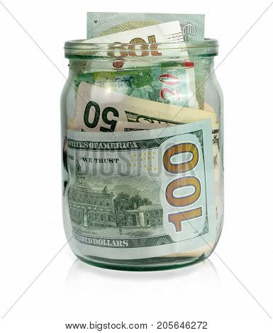 Different currency in a glass jar on a white background