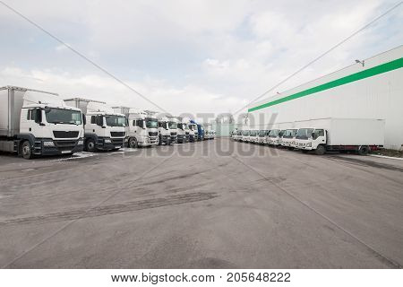 cargo vehicles stand in a row on a parking lot near the factory warehouse. freight transportation. truck in the warehouse