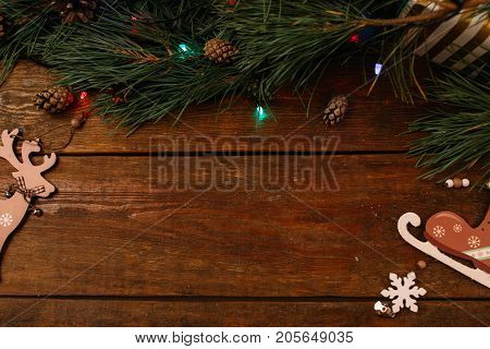 Festive background of winter holidays decoration. Pine branch, fairy lights and handmade ornaments on wooden table, top view copy space. Celebration, New Year, Christmas, homemade decor concept