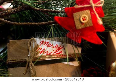 Festive background of Christmas presents. Close up handmade striped package with greeting memo and red felt fir tree. New Year traditions and congratulation concept