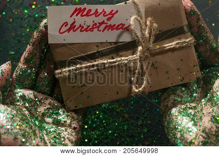 Festive backdrop of Christmas present. Gift bag with greeting memo and holiday sparkles holding in woman's glittering hands on black background, pov view. Happy celebration, congratulation concept