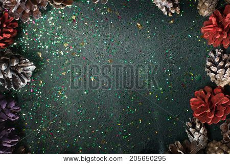 Festive backdrop for Christmas gift and greeting. Top view sparkled black background with strobilas around, free space in the middle. Celebration, presents and congratulation concept