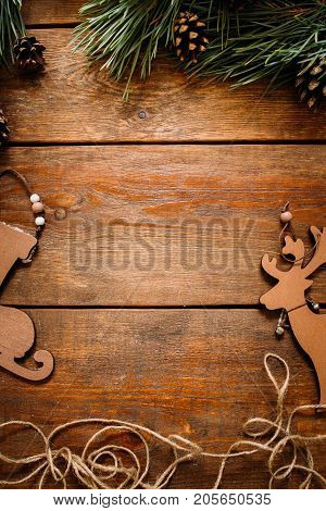 Christmas and New Year holiday background. Close up handmade ornaments of skate and deer and pine with strobila above on wooden table, festive decoration concept. Free space in the middle