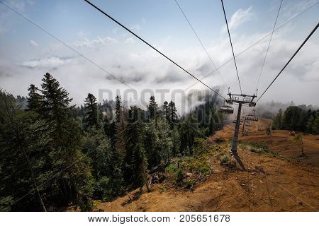 View from top of ropeway with multiple seats and stretched cables above trees in deep fog. Mountains of the North Caucasus