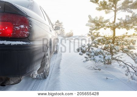 A car driving on a snowy rural road