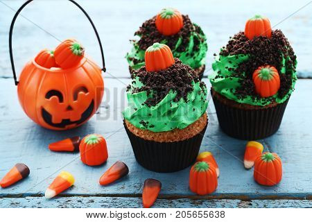 Halloween Cupcakes With Candies On Blue Wooden Table