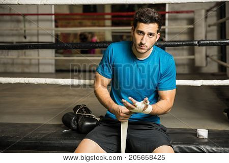 Portrait of a good looking Hispanic young man wrapping his hands and getting ready for training in a boxing gym