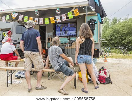 QuievyFrance - July 07 2015: Unidentified spectators watching on a TV the live transmission near their caravan during the stage 4 of Le Tour de France 2015 in Quievy France on 07 July2015.