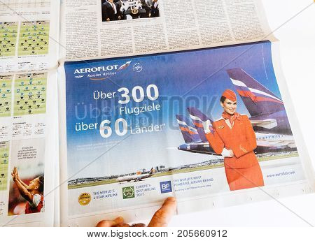 PARIS FRANCE - SEP 25 2017: Man reading German newspaper looking at advertising from Aeroflot Russian Airlines latest offers