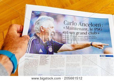 PARIS FRANCE - SEP 25 2017: Man reading international newspaper Sport edition about Carlos Ancelotti currently manager of German club Bayern Munich