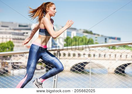 Close-up picture of active young woman sprinting across the city