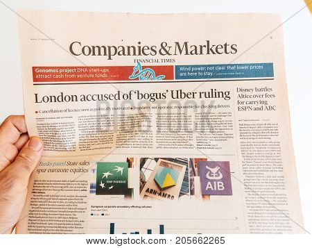 PARIS FRANCE - SEP 25 2017: Man reading international newspaper Financial Times Companies and Market London accused of bogus Uber ruling