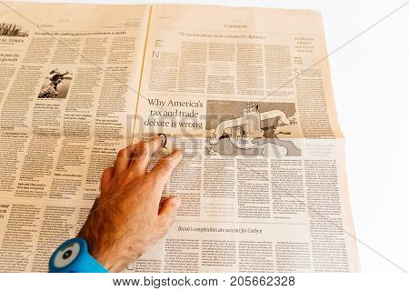 PARIS FRANCE - SEP 25 2017: Man reading international newspaper Financial Times - why America tax and trade debate is wrong